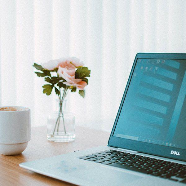 black-and-gray-dell-laptop-beside-white-ceramic-mug-flower-1989304